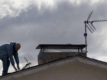 Un operario cambia la antena en el tejado de una vivienda unifamiliar en Manzanares el Real (Madrid).