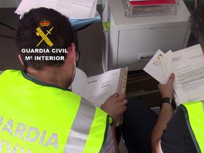 Agentes de la Guardia Civil revisan documentación intervenida en  2016 a la trama financiera desmantelada ahora por segunda vez.