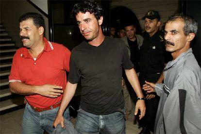 En la imagen, el fotógrafo español es fuertemente custodiado tras su liberación.