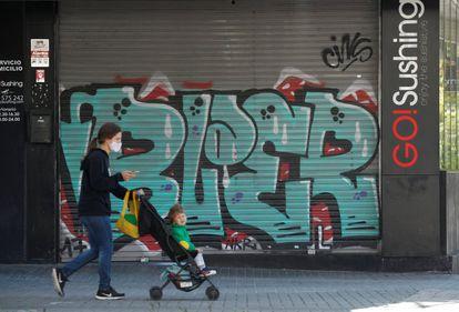 Una mujer pasa junto a un restaurante cerrado, en el centro de Barcelona.