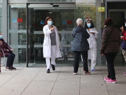 Varias trabajadoras sanitarias hablan con pacientes que esperan en la puerta de un Centro de Salud en Coslada, Madrid (España), el pasado noviembre.