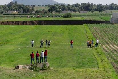 Decenas de personas observan el sumidero en Santa María Zacatepec, Puebla.