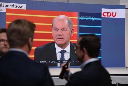 Militantes de la CDU siguen en la sede en Berlín el debate entre candidatos, con el socialdemócrata Olaf Scholz en pantalla.