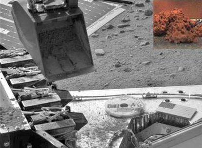 Imagen del brazo de la sonda Phoenix recogiendo material del suelo de Marte. En la parte superior izquierda, en rojo, una muestra de suelo marciano facilitada por la NASA.