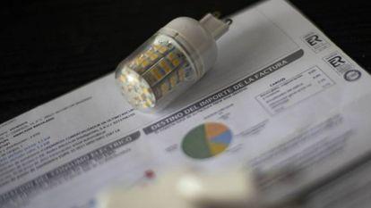 Una bombilla, sobre una factura de la luz.