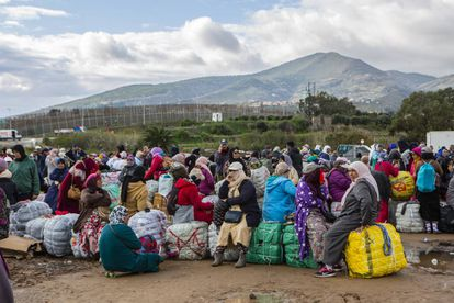 Un grupo de porteadoras espera al autobús que les llevará desde los polígonos de Melilla a la frontera, en el Barrio Chino.