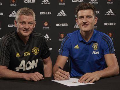 Harry Maguire firma su contrato acompañado del entrenador del United, Ole Gunnar Solskjaer.