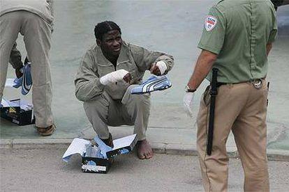 Un inmigrante herido que entró ayer en Ceuta pide ayuda a un guarda jurado para ponerse las zapatillas.