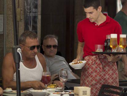 Un camarero sirve a unos clientes en un bar de Ronda.