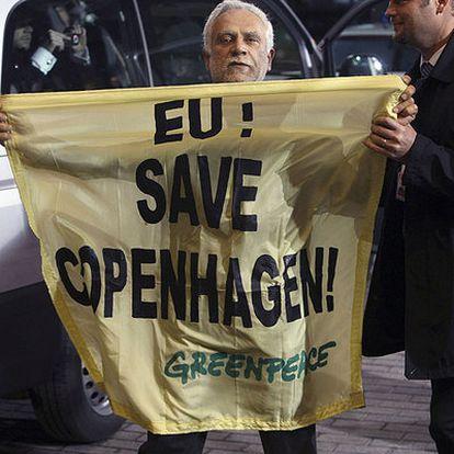 """Un activista despliega una pancarta que lee """"UE: salva a Copenhague"""", en referencia a la cumbre del clima"""