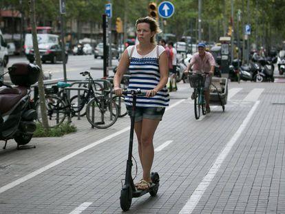 Una mujer en patinete por la ciudad.