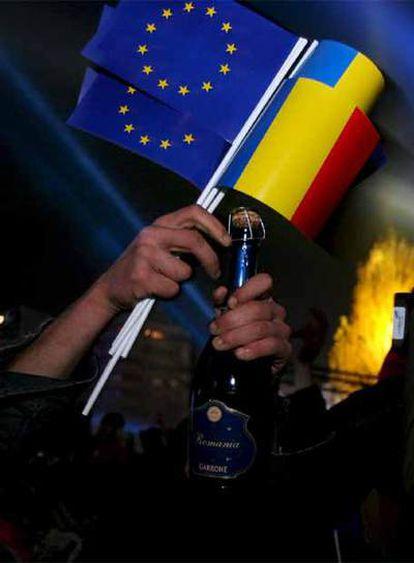 Un ciudadano rumano con las banderas de la Unión Europea y de su propio país descorcha una botella de champán para celebrar el ingreso de Rumanía.