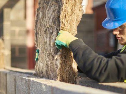 Un trabajador de la construcción coloca una manta de aislamiento térmico en la cavidad de un muro.