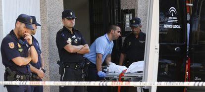Los servicios funerarios trasladan una víctima desde la escena del crimen.