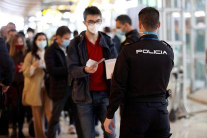 Un agente de la policía controla el paso de viajeros en el aeropuerto de Barajas, en Madrid, el 19 de marzo.