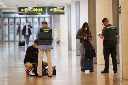 Agentes de la Guardia Civil realizan un control a viajeros procedentes de Ámsterdam a su llegada al aeropuerto de El Prat, este martes.