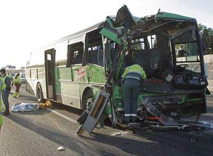 La Guardia Civil de Tráfico inspecciona el autocar de la empresa Larrea accidentado ayer en la autovía de A Coruña (A-6). A la izquierda, el cadáver tapado de María Re.