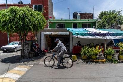 José de Jesús Padilla y José Luis Sánchez, sentados en una banca junto a un puesto de tacos en el barrio Granjas Estrella.