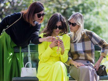 Tres mujeres revisan un teléfono móvil.