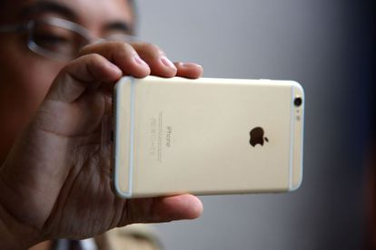 Un hombre sujeta un iPhone 6, un teléfono de Apple.