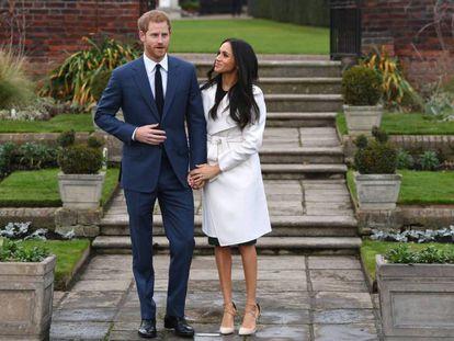 El príncipe Enrique de Inglaterra posa junto a su prometida, la actriz estadounidense Meghan Markle, tras anunciar su compromiso en el Jardín Sunken del Palacio Kensington.
