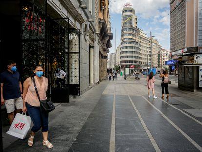 Varias personas salen de una tienda de H&M en Gran Vía.