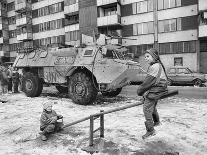 Dos niños juegan durante el cerco de Sarajevo ante un blindado de Naciones Unidas.