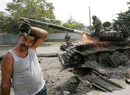 Un trabajador corta con un soplete el cañón de un tanque georgiano destrozado durante los enfrentamientos de este mes en Osetia del Sur.