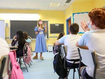 Una profesora con un grupo de niños del colegio Maestro Padilla, en Madrid, (España).