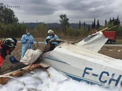 Varios bomberos junto a la avioneta accidentada en Vélez-Málaga.