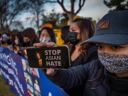 """Una mujer sostiene un móvil con la frase """"detengan el odio a los asiáticos"""" en una vigilia este miércoles, en California."""