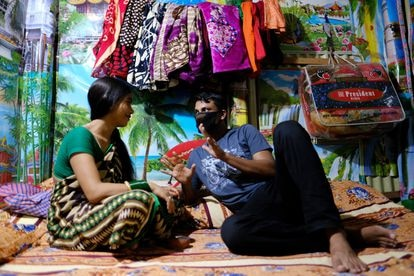 La trabajadora del sexo Sewali (izquierda) charla con un cliente en su habitación del burdel de Kandapara, en Tangail.
