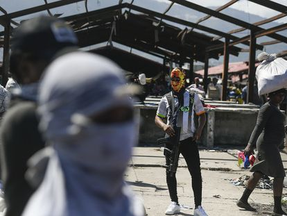 Un miembro armado de la pandilla G9 hace guardia durante una concentración.
