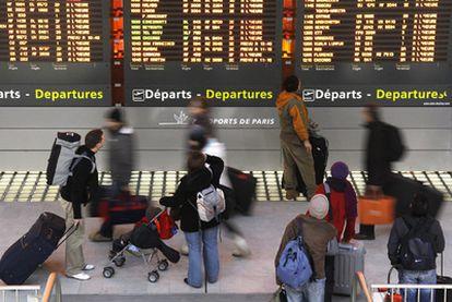 Pasajeros frente a los paneles de información del aeropuerto Charles de Gaulle.