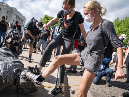 Dos manifestantes pisan la cabeza de una estatua de Cristóbal Colón en St. Paul, Minnesota, en junio de 2020.