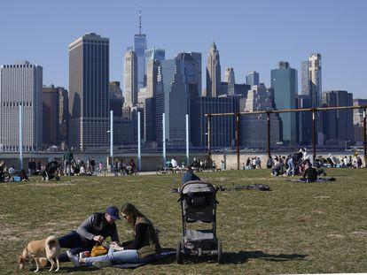 Un grupo de ciudadanos descansa en el barrio neoyorquino de Brooklyn con Manhattan al fondo, el pasado domingo.