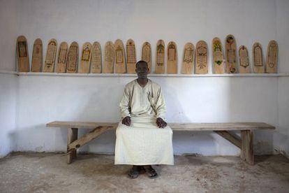 Aboubakar Yaro, jefe de conservación de la Biblioteca de Djenne (Malí), delante de algunos manuscritos sobre madera del Corán.