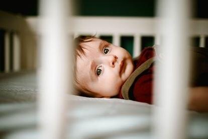 Un bebé despierto en su cuna.