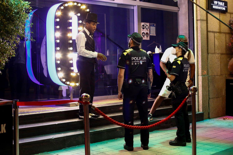 Una patrulla de la Guardia Urbana de Barcelona conversa con un trabajador de un local de ocio nocturno, el pasado 26 de julio.