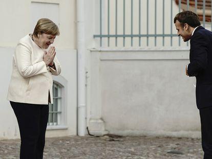 La canciller alemana, Angela Merkel, y el presidente francés, Emmanuel Macron, se saludan desde la distancia a las puertas del castillo de Meseberg, el lunes, al norte de Berlín.