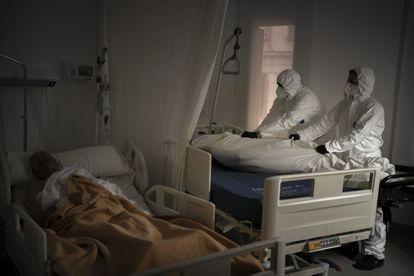 Los trabajadores de una funeraria trasladan a un fallecido por coronavirus en una residencia de mayores de Barcelona mientras otro anciano duerme.