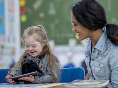 Una niña con Sindrome de Down con su profesora.