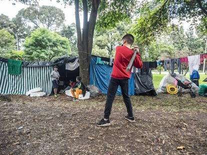 Un niño practica béisbol en un campamento improvisado por migrantes venezolanos, en Bogotá.