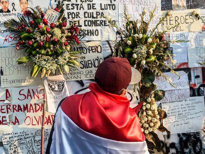 Un hombre con una bandera peruana frente a un homenaje a los dos jóvenes que murieron en las protestas en Perú.