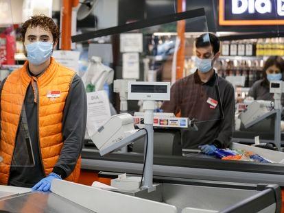 Adrián, 21, estudiante y empleado de un supermercado Día & Go en Madrid posa junto a las cajas.