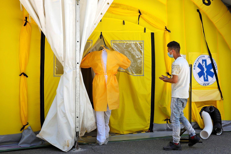 Un sanitario y un paciente entran en el hospital de campaña instalado ante el CUAP Prat de la Riba de Lleida, este jueves.