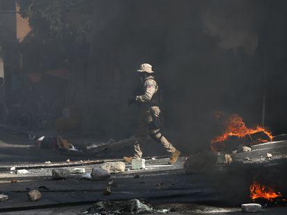 Un policía despeja una carretera bloqueada por manifestantes en el barrio Lalue de Port-au-Prince, Haití, el miércoles 14 de julio de 2021.