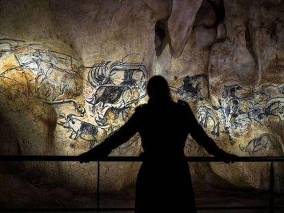 Una persona contempla la reproducción de las pinturas de la cueva de Chauvet (Francia).