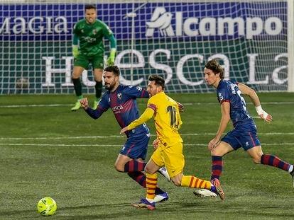 Messi conduce ante la presión de los jugadores del Huesca.