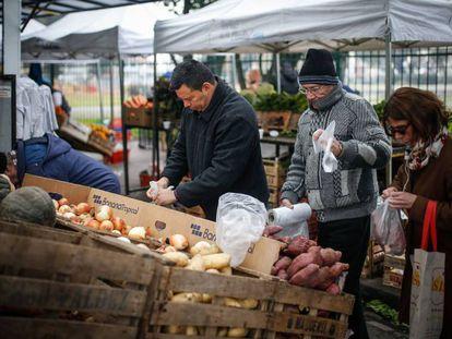 Un grupo de personas compra en un puesto callejero de frutas y verduras en Buenos Aires.